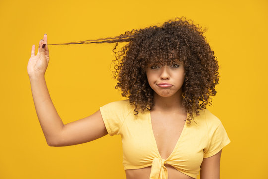 Closeup unhappy frustrated young woman surprised she is losing hair, receding hairline. Yellow background. Human face expression emotion. Beauty hairstyle concept. Curly hair girl. Brazilian.