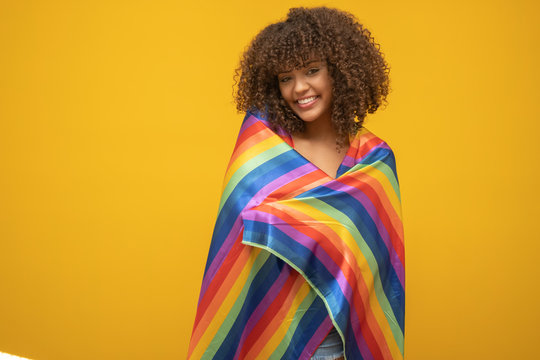 Young curly hair woman covering with lgbt pride flag. Alone. One. Keeping fist up, covering LGBT flag. LGBT+ flag on yellow background.