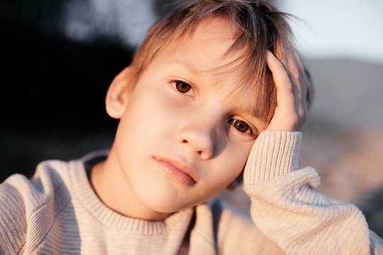 Portrait of pensive boy with head in his hand