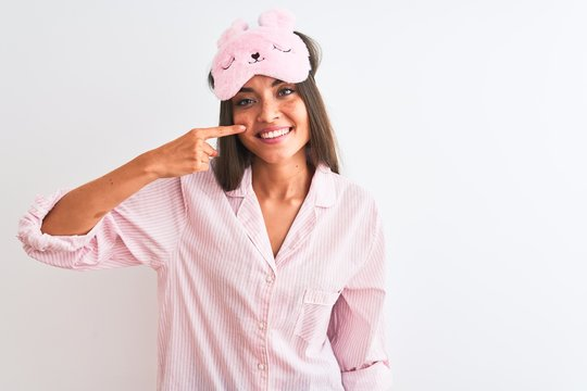 Young beautiful woman wearing sleep mask and pajama over isolated white background Pointing with hand finger to face and nose, smiling cheerful. Beauty concept