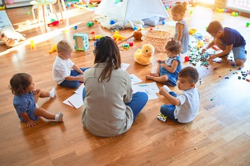 Beautiful teacher and group of toddlers sitting on the floor drawing using paper and pencil around...