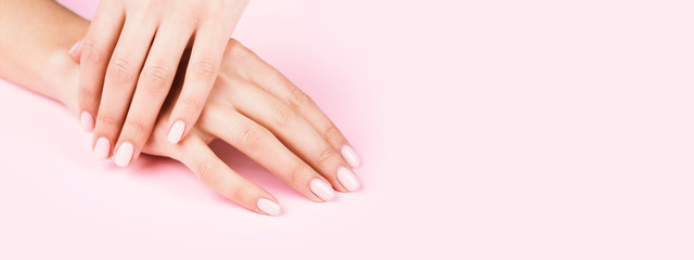 Female's hands with classic pastel manicure on pink background.