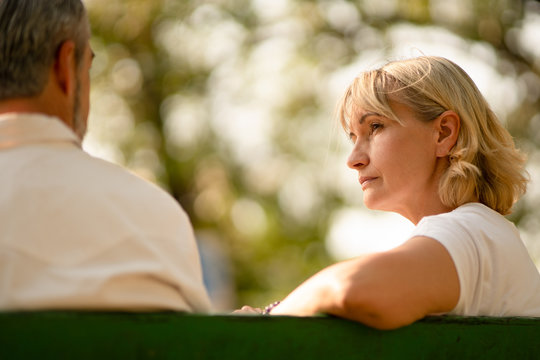 Senior caucasian woman looks pensive and worried while concentrate discuss problem with her husband in the park, elderly discussion, listening and support couple, love and compassion family concept.