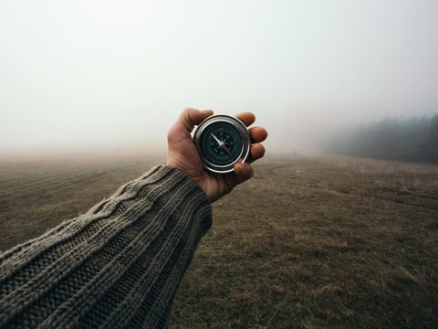Man explorer searching direction with compass in the foggy field