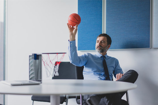 Mature businessman playing basketball in office