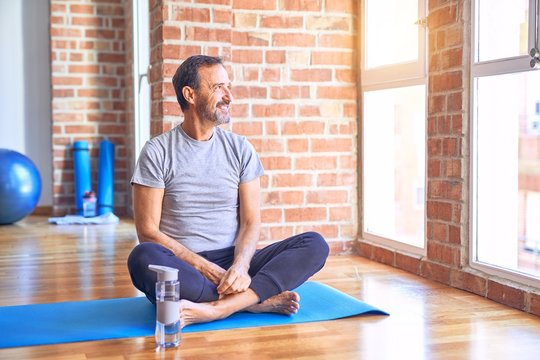 Middle age handsome sportman sitting on mat doing stretching yoga exercise at gym looking away to side with smile on face, natural expression. Laughing confident.