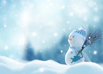 Wall Mural - Merry Christmas and happy New Year greeting card with copy-space. Happy snowman with a broom in hand, standing in Christmas landscape. Snow background. Winter fairytale.