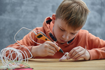 Boy makes volume plastic figures with 3D pen. STEM educational toy for kids at home and school. Play and study