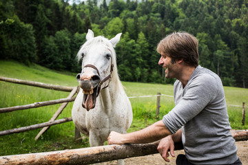 Germany, Bavaria, Bad Toelz, man with horse at fence