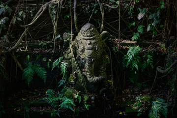 Statue of ganesh covered in moss and ferns in bali