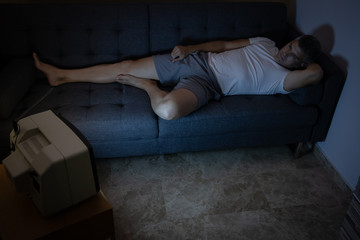 A man is watching TV on the couch at night with no lights