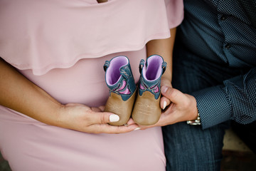 Mom and dad to be holding baby boots