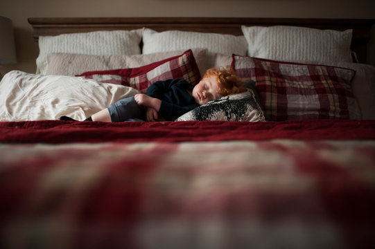 Toddler boy asleep on red plaid bed in pillows at home