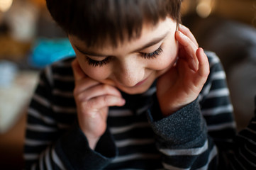 Boy 7-8 years old with long eyelashes looking down with hands by face