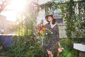happy woman holding flowers in urban garden