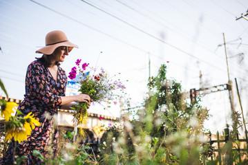 woman in an urban garden picking flowers