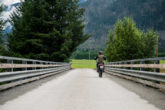 A woman rides her motorcycle across a bridge on a cloudy summer day.