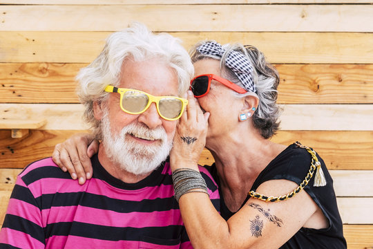 Youth people caucasian couple of cheerful alternative senior whispering secrets and enjoy the life togther - wood background and youthful retired lifestyle