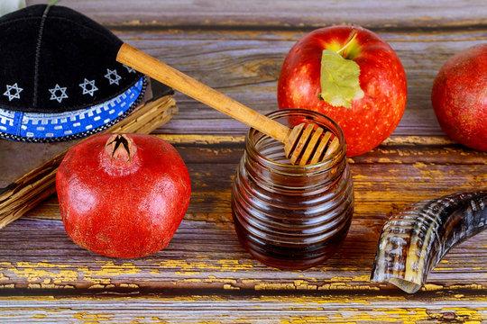 Honey on the pomegranate and apples. Jewish new year Rosh Ha Shana kippah yamolka and shofar
