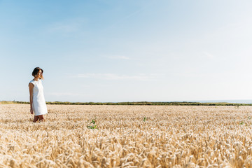 Woman stand in golden field during a sunny day
