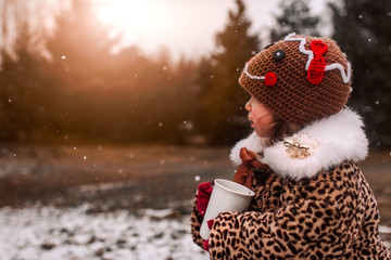 Little girl bundled up drinking hot chocolate on a cold winter day