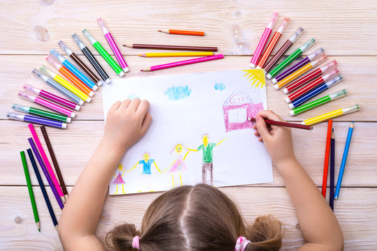 A child draws a birthday card with his family. Drawing made by a child with colorful felt-tip pens and pencils. Happy family. Child's drawing
