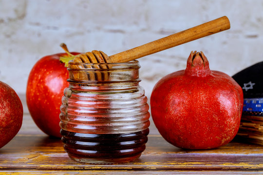 Pouring honey on apple and pomegranate with honey symbols of Jewish New Year - Rosh Hashanah.