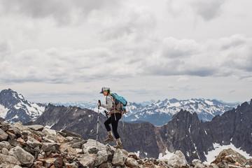 A female hiker walks amid the snowy peaks of the Cascades, Washington