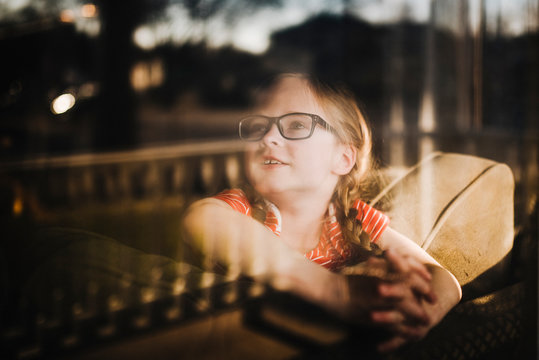 Front view of little girl looking out of window with reflections