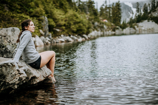 a female hiker dips her toes in Snow Lake, Snoqualmie Pass, Washington