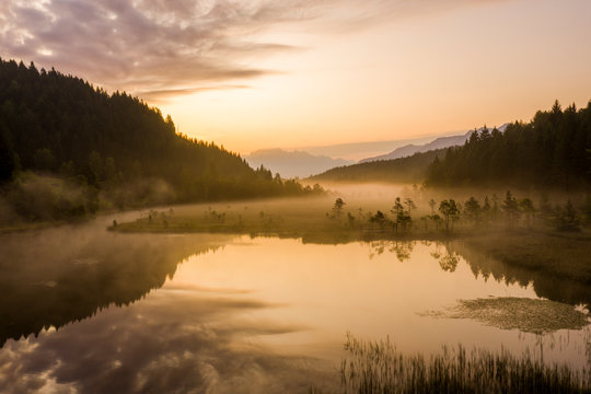 Sky painted orange at dawn with misty land of Pian di Gembro nature Reserve, aerial view, Aprica, Valtellina, Lombardy