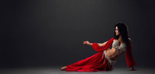 Woman in red arabic dress dancing oriental dances in stalls