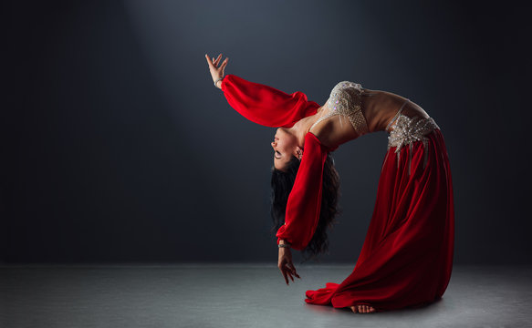 beautiful black-haired girl in red ethnic dress dancing oriental dances leaning back