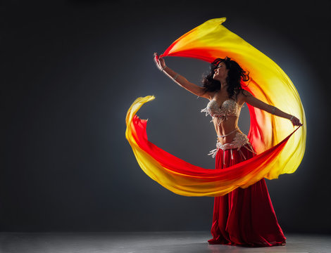 beautiful black-haired girl in red ethnic dress on the stage dances oriental dancing waving fabric in her hands