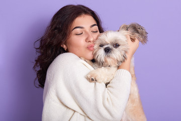 Horizontal picture of magnetic charming black haired woman with pet in her hands, hugging her domestic animal, kissing it with closed eyes, wearing white sweater, posing over lilac background.