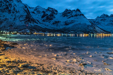 Lofoten islands, Norway. Fantastic view of icy coast of fjord in winter with snow and ice under the moon light. Snowy mountains and the road in the background. Travel Norway.
