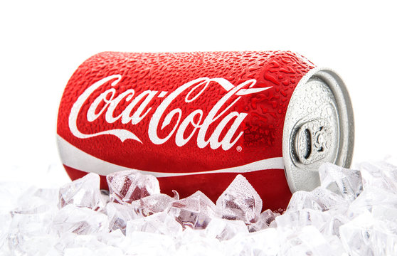 Can of Coca-Cola on a bed of ice over a white background