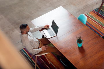 High angle view of young businessman using laptop at table in office