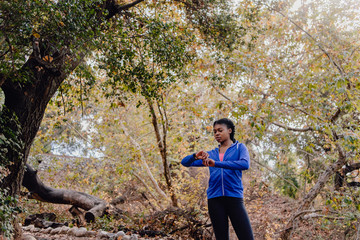 Young sporty woman checking pulse on stopwatch at forest