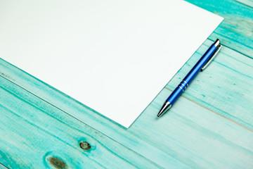Obraz Niebieski długopis i kartka na turkusowym tle - fototapety do salonu