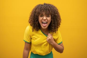 Brazil supporter. Brazilian woman fan celebrating on soccer / football match on yellow background. Brazil colors.