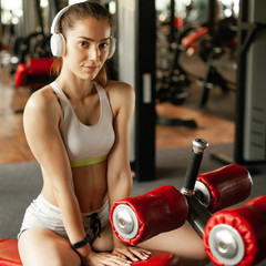 In de dag Ontspanning Close up portrait of young pretty european fitness woman at the gym and listen music in headphones. Breaking relax while exercise workout. Concept of health and sport lifestyle. Athletic Body...