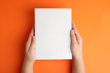 Woman holding book with blank cover on orange background, top view