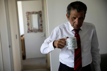 Gino Rojas holds a cup of coffee as he checks notes at his house in Santiago