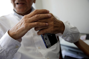 Gino Rojas holds his cellphone as he speaks during an interview with Reuters at his house in Santiago