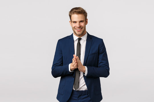 Time to make money. Corporate, finance and business concept. Good-looking blond bearded businessman, smiling pleased and lucky, relish good deal, rub hands, expect big news, white background