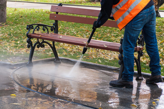 cleaning the park with water in autumn. A worker cleans the park
