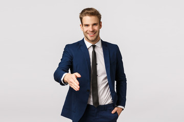 Entrepreneur, business and corporate concept. Attractive confident, smiling young blond businessman, extend arm for handshake say nice to meet you, greeting partners discuss income and deals