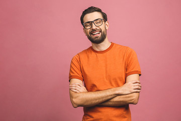 Happy young man. Portrait of handsome young man in casual keeping arms crossed and smiling while standing against pink background.