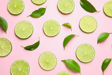 Juicy fresh lime slices and green leaves on pink background, flat lay